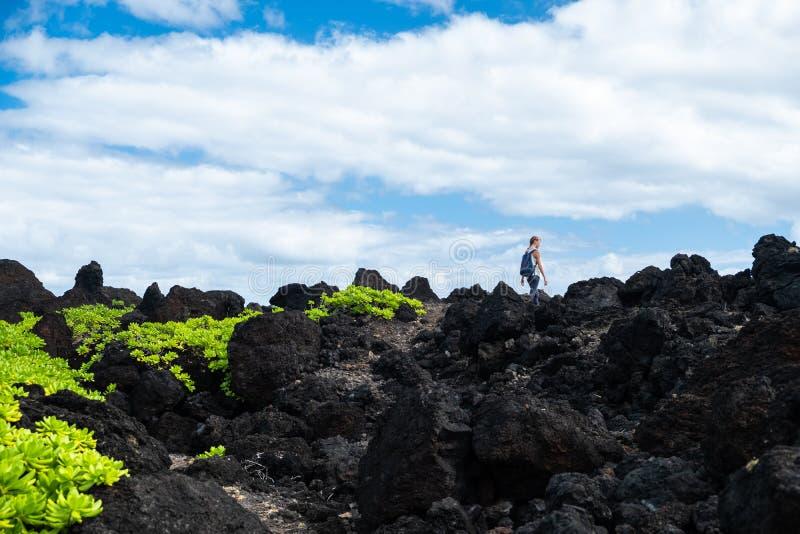 Woman hiker walks on the sharp volcanic land. Maui, Hawaii stock images