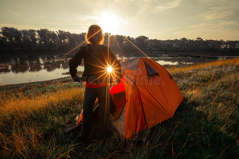 Woman hiker. Wears sweater as she gets out from the tent set on the river coast and enjoys calm sunrise stock photo