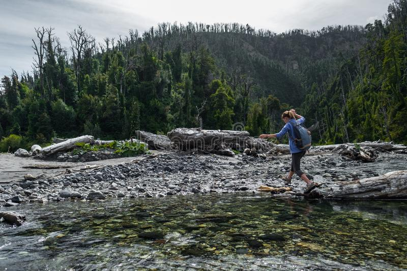 Woman hiker. Crossing the small river in the wild area stock image