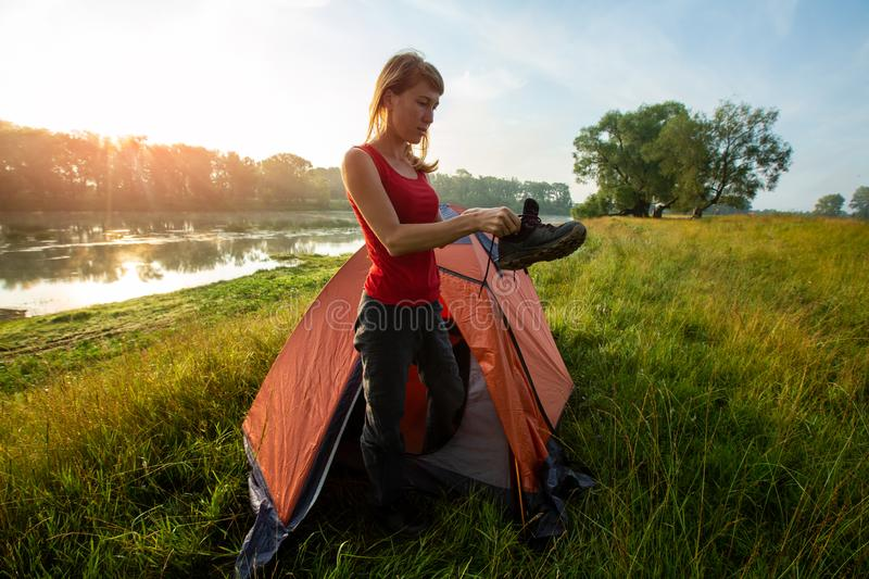 Woman hiker. Stands near the tent and wears her shoe with sun shining through the trees on the background royalty free stock photos