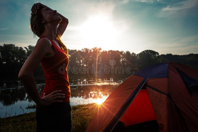 Woman hiker. Young woman hiker stands near the tent and enjoys sunrise royalty free stock image