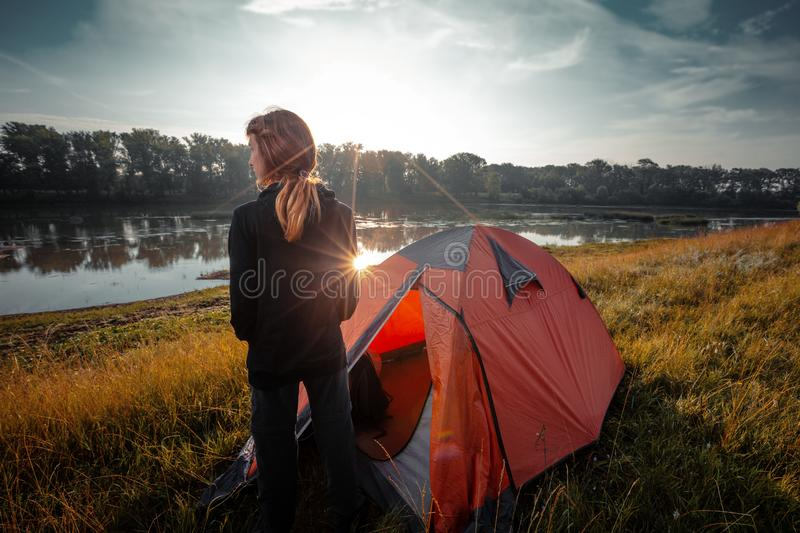 Woman hiker. Young woman hiker stands near the tent and enjoys sunrise over the river royalty free stock photo