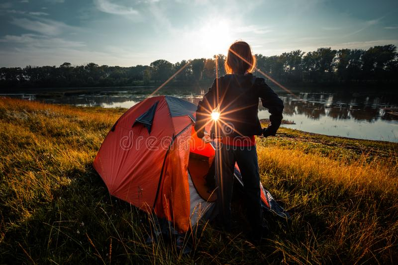 Woman hiker. Young woman hiker stands near the tent and enjoys sunrise over the river royalty free stock image