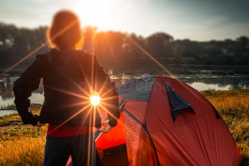 Woman hiker. Young woman hiker stands near the tent and enjoys sunrise over the river. Tilt shift effect applied royalty free stock images