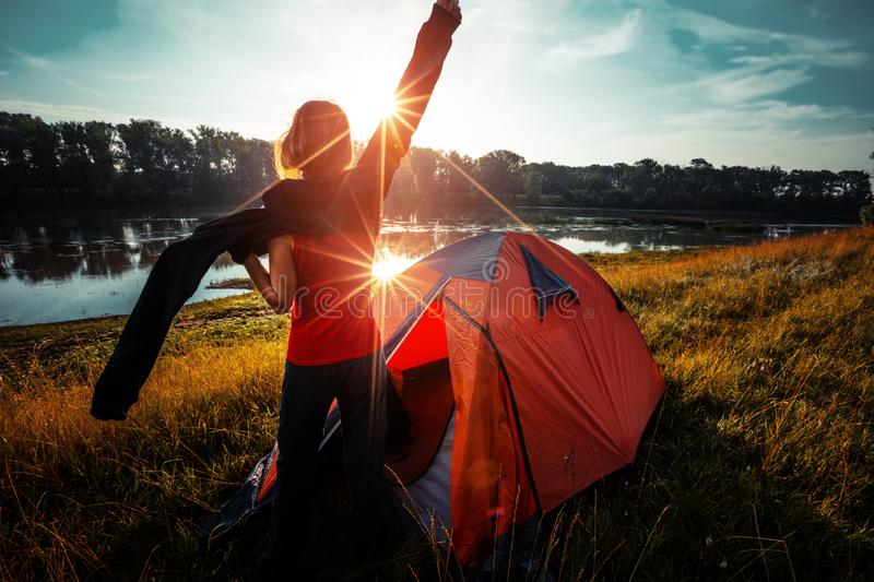 Woman hiker. Young woman hiker stands near the tent wears sweater and enjoys sunrise over the river royalty free stock photography