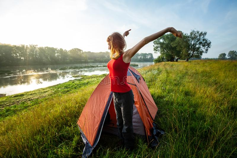 Woman hiker. Young woman hiker stretches near the tent and greets the sun royalty free stock photo