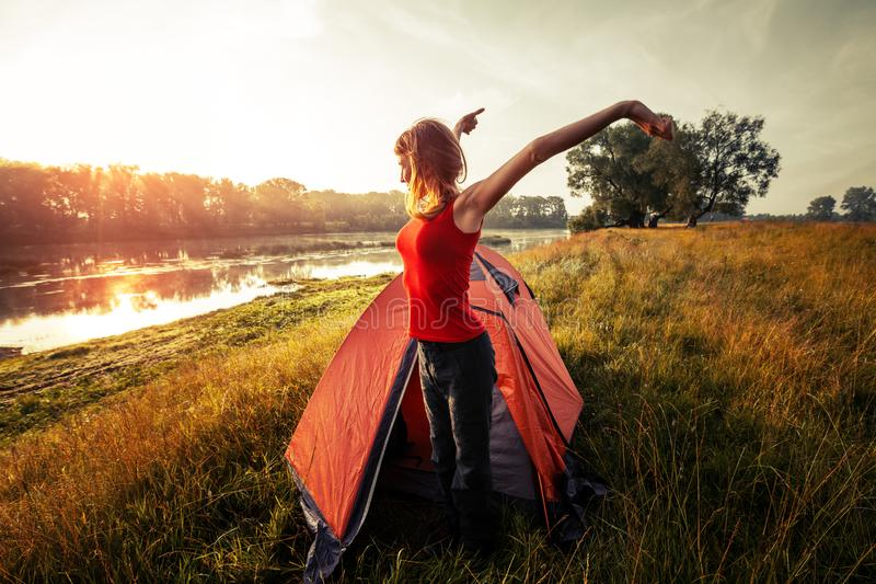 Woman hiker. Young woman hiker stretches near the tent and greets the sun stock photo
