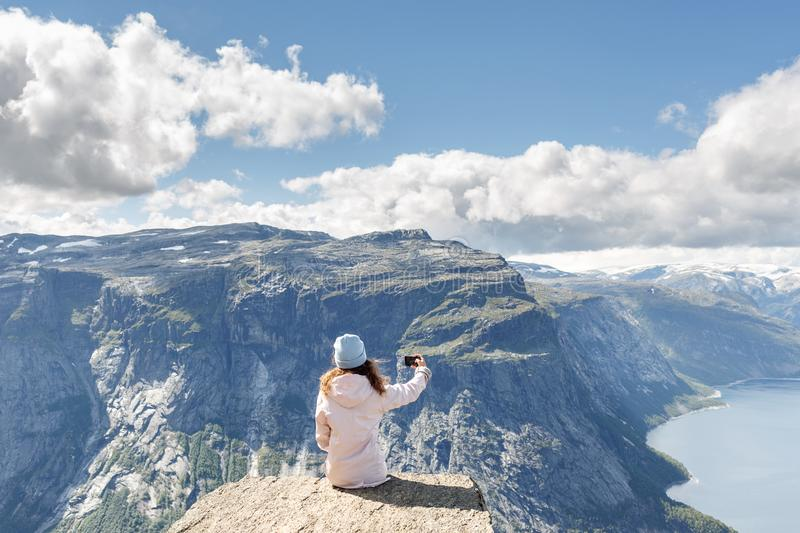 Woman hikers making selfie use smart phone while relaxing on cliff at mountain top with blue water fjord on background. Happy woman hikers making selfie use stock photography