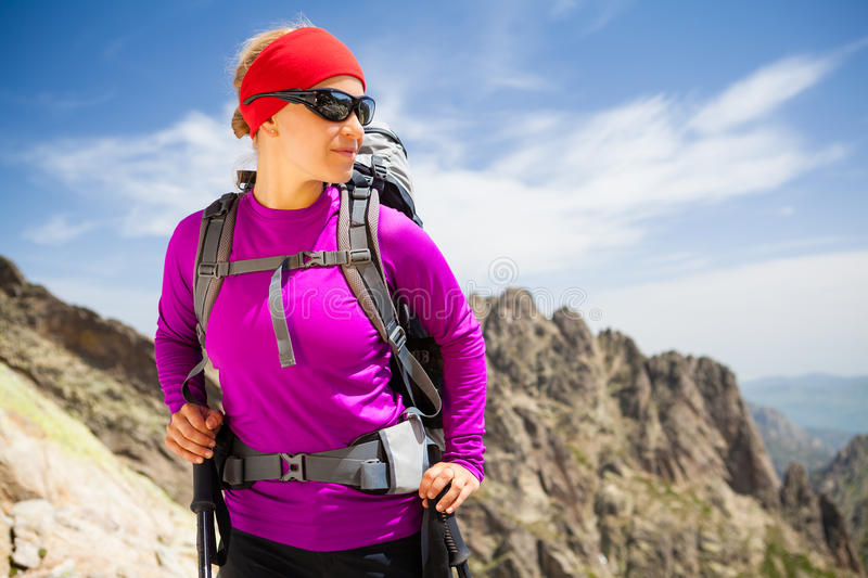 Woman hiking with backpack in inspirational mountains. Female caucasian trekker hiker tourist looking from mountain top to beautiful scenic view. Sport and stock photos