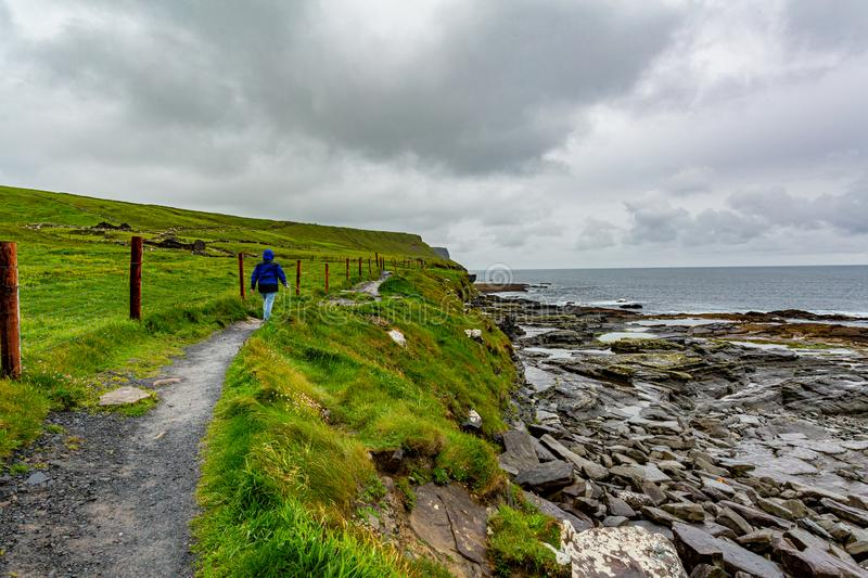 Woman hiking from Doolin to the Cliffs of Moher along the coastal walk route. Geosites and geopark, Wild Atlantic Way, spring day in the countryside in County stock photos