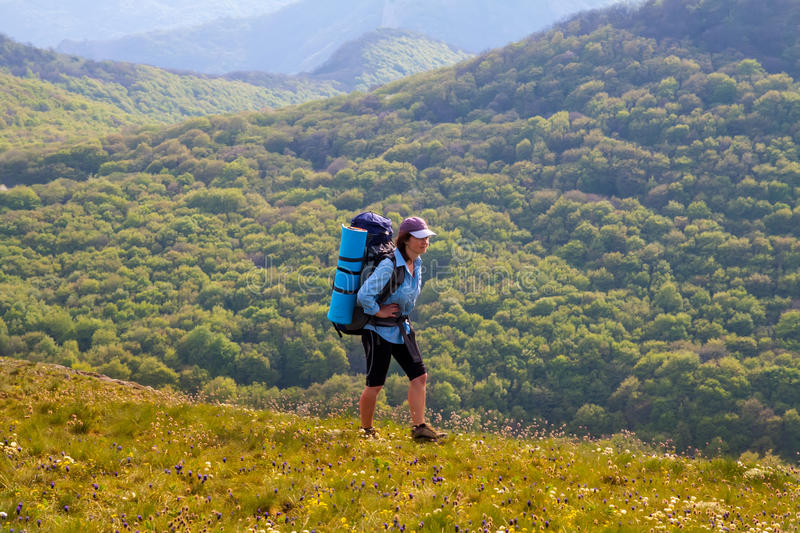 Woman hiking on forest and mountain background stock image