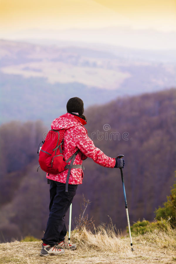 Woman hiking in a high mountain and looking the beautiful orange sunset sky. Hiker woman with backpack and walking sticks in a high winter mountain.Beautiful royalty free stock photos