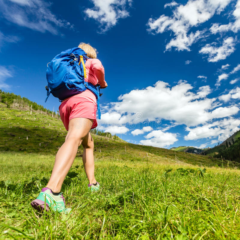 Woman hiking in mountains, adventure and travel. Woman hiking and walking in mountains with backpack. Travel and trekking in beautiful summer nature, inspiring royalty free stock images