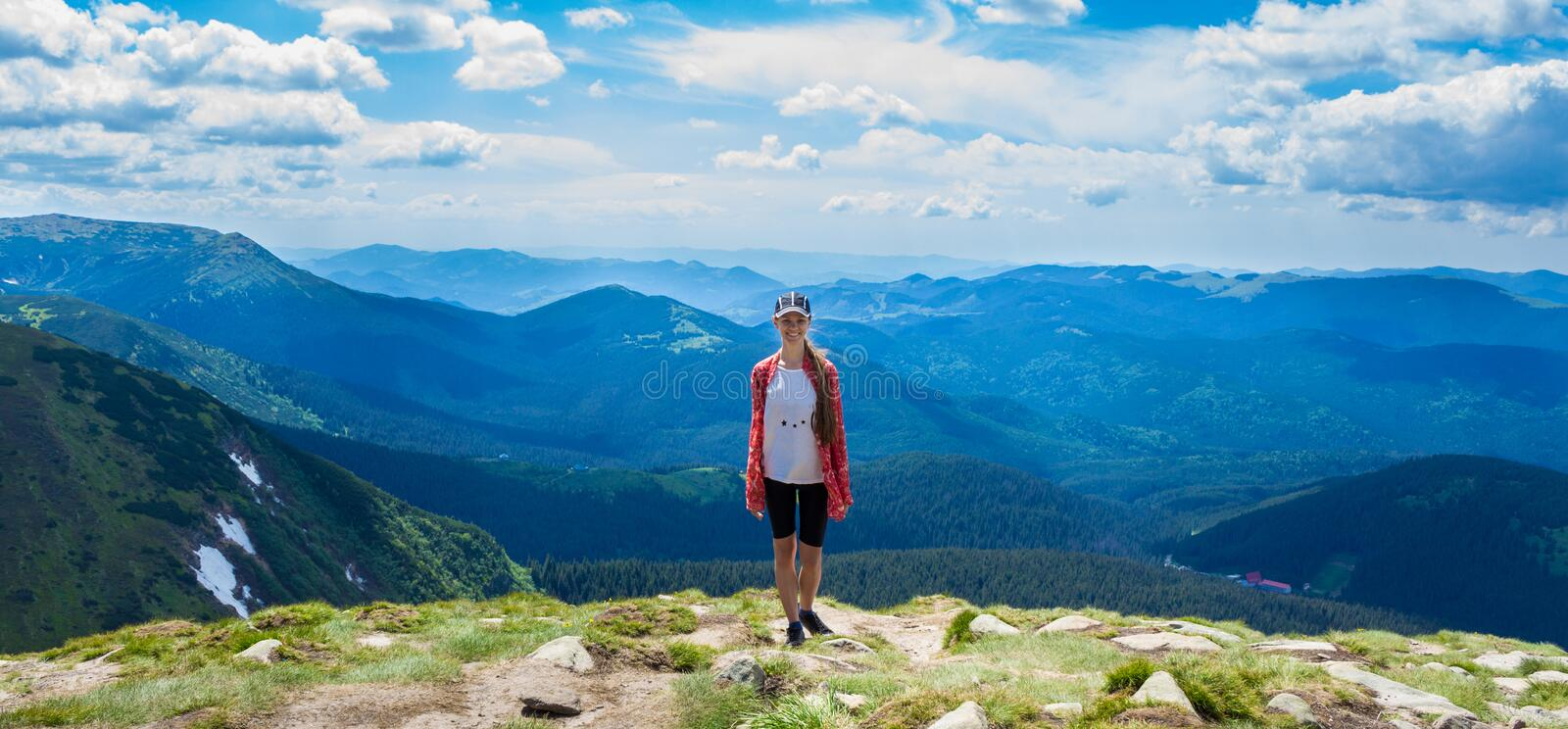 Woman hiking in mountains at sunny day royalty free stock photography
