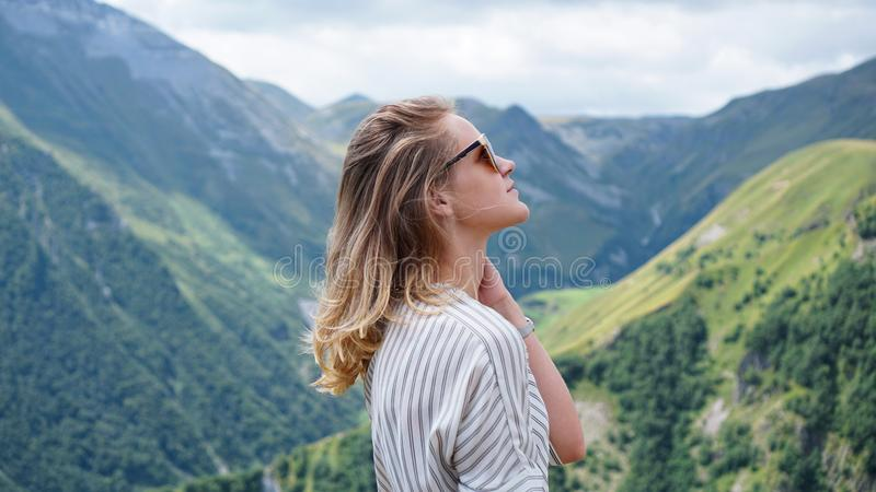 Woman hiking in mountains at sunny day time royalty free stock image