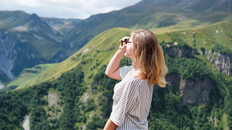 Woman hiking in mountains at sunny day time stock photo