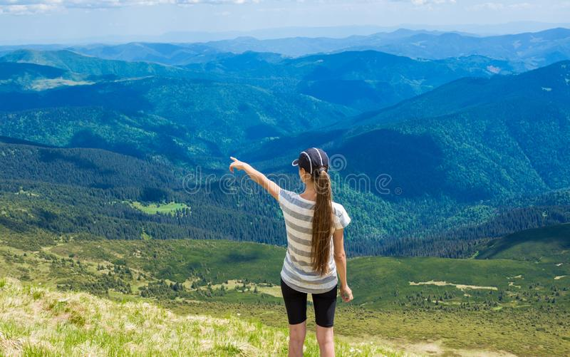 Woman hiking pointing to the sky enjoy the beautiful view at mountain royalty free stock images