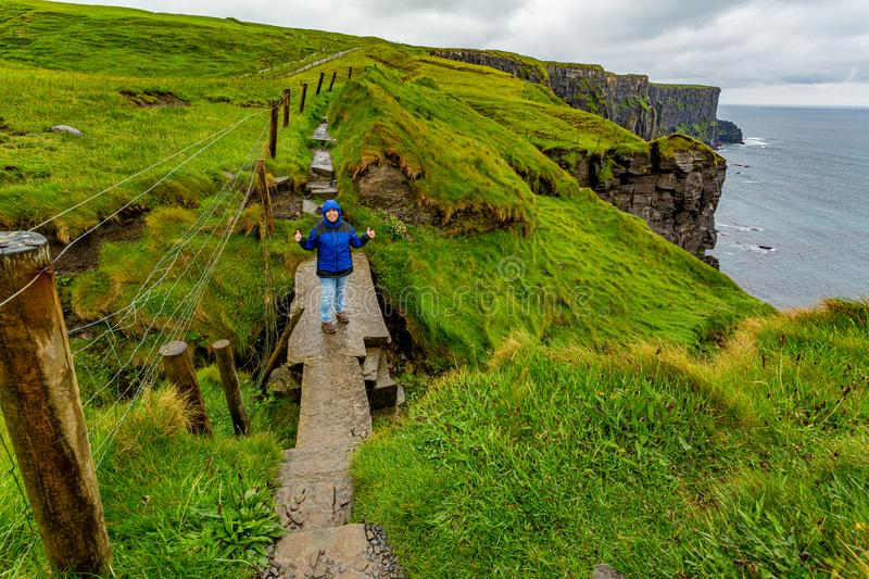 Woman hiking on a rainy day from Doolin to the Cliffs of Moher along the spectacular coastal route walk. Geosites and geopark, Wild Atlantic Way, spring day in stock photos