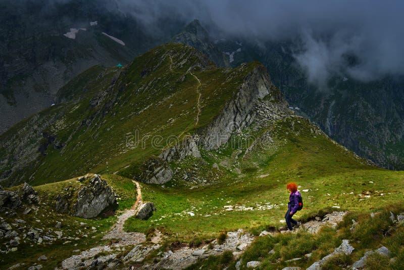 Woman hiking into rocky mountains stock photos