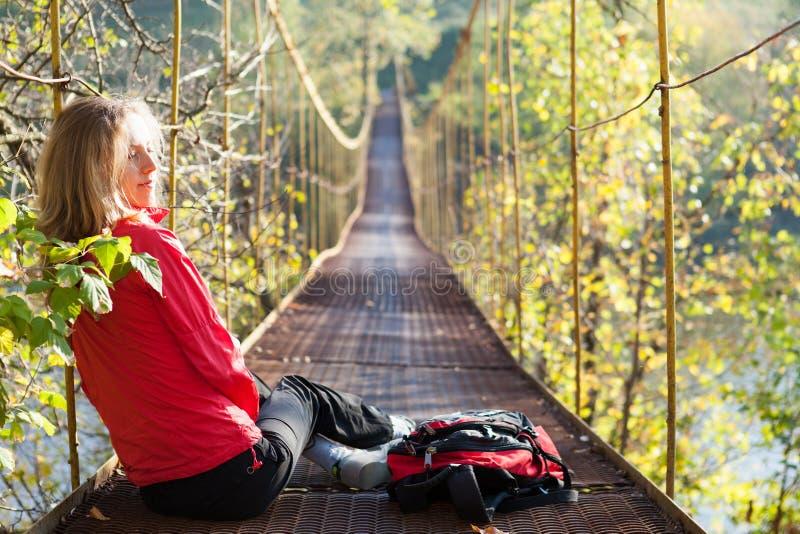 Woman hiking sitting in suspension bridge
