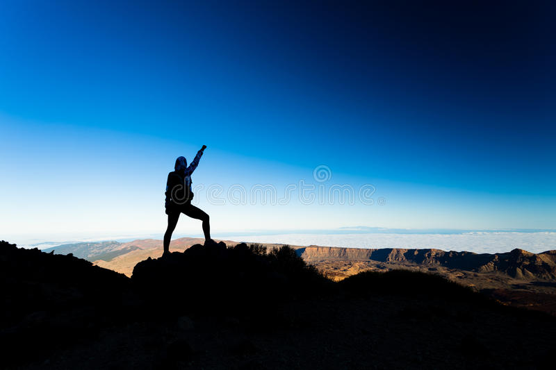 Woman hiking success silhouette on mountain top stock images