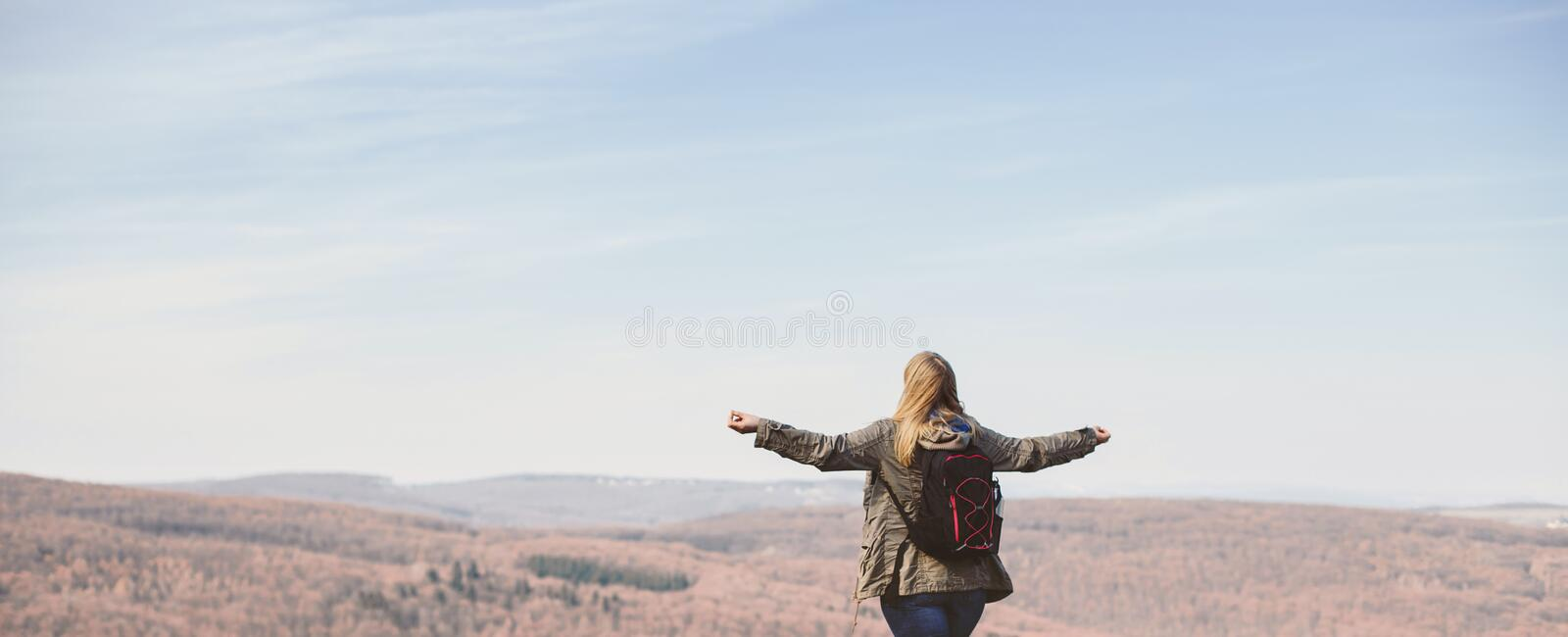 Woman is hiking and trekking outside on a hill. Tourism, vacation and fitness activity concept stock photo