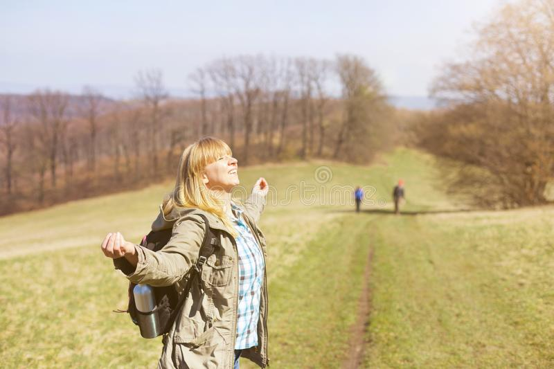 Woman is hiking and trekking outside on a hill. Tourism, vacation and fitness activity concept royalty free stock images