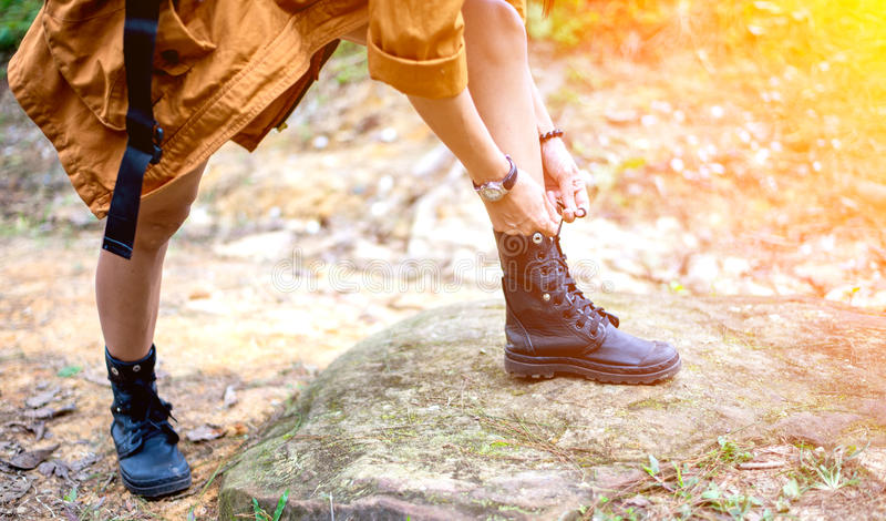 Woman hiking tying shoelace on forest trail stock photography