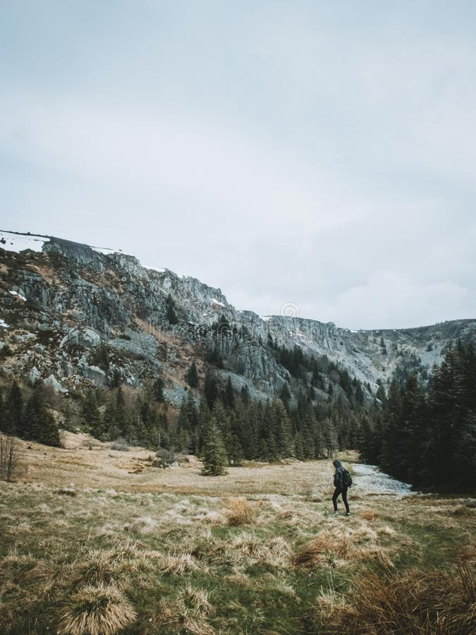 Woman hiking through a valley on a mountain with green trees and snow on the top. With green grass and a beautiful scenery royalty free stock photo