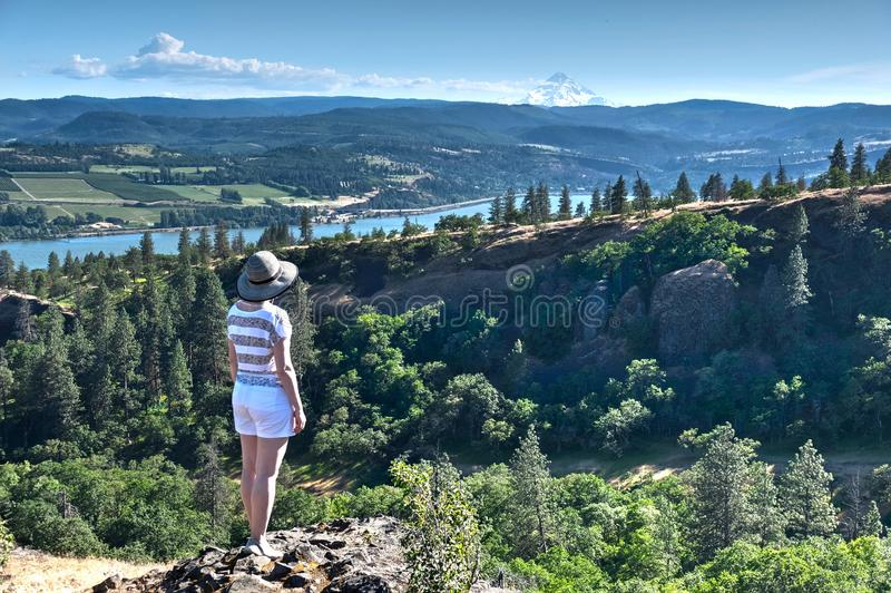 Woman hiking in valley with view of Mount Hood. stock image