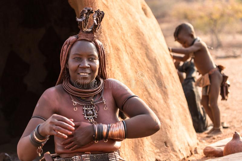 A woman from the Himba tribe cleansing herself in front of her hut, Epupa falls, Namibia stock photos