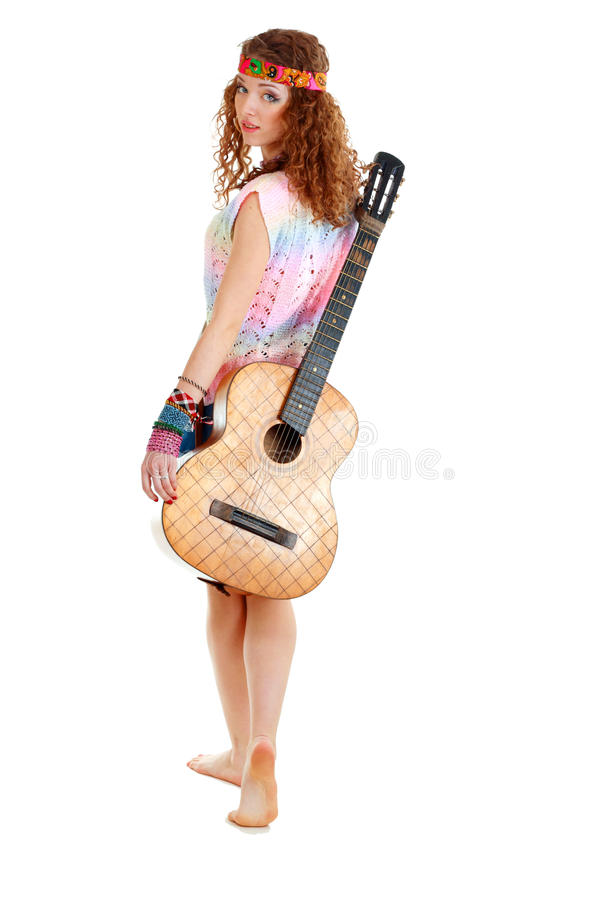 Woman in hippie outfit walking with guitar
