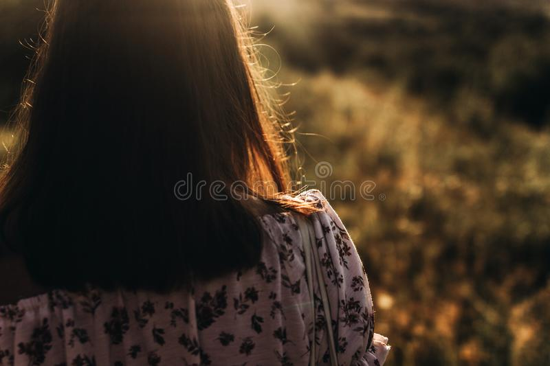 Woman hipster hair at sunset in summer field. back view. atmospheric moment. boho girl relaxing in meadow in beautiful sunlight. Vacation and travel royalty free stock images