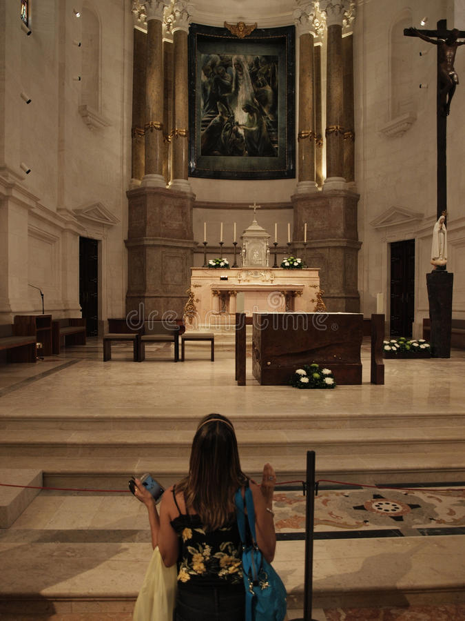 WOMAN ON HIS KNEES PRAYING INSIDE BASILIC. A young woman praying on his knees to Our Lady of Fátima in front of main altar stock photography