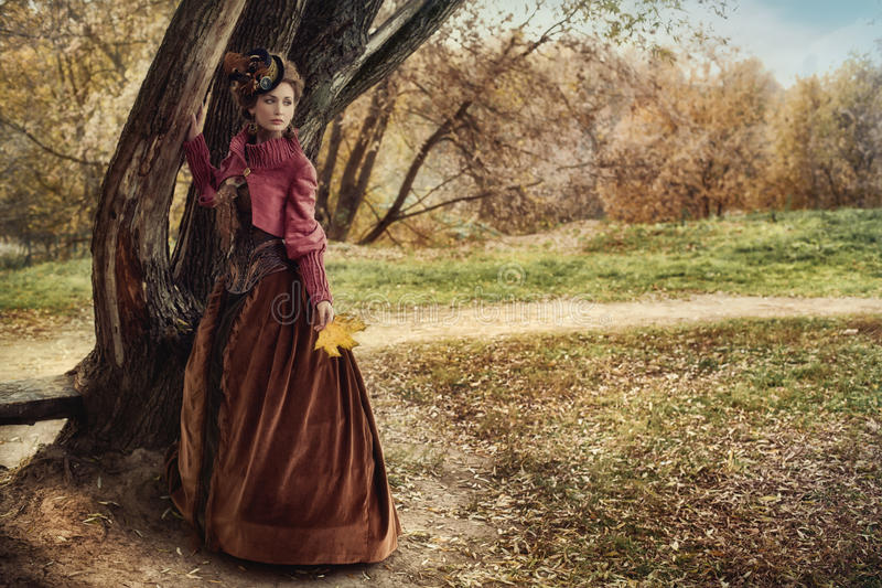 Woman in historical dress near the tree in autumn forest. Woman in a historical costume standing near a tree in autumn forest stock photography