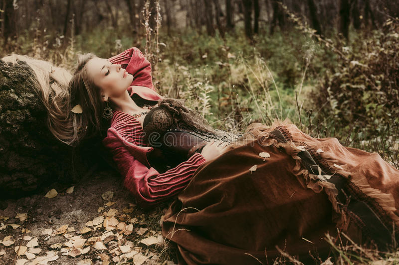 Woman in historical dress resting in autumn forest. stock photo