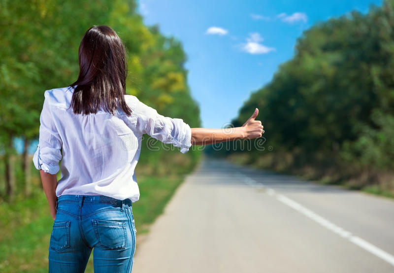 Woman hitchhiking back view. Nature background stock photos