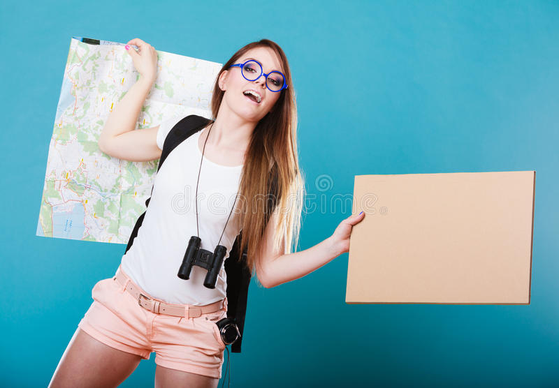 Woman hitchhiking with blank sign for your text. Travel and tourism active lifestyle concept. Woman tourist hitchhiking with blank sign for text on blue stock photos