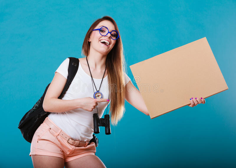 Woman hitchhiking with blank sign for your text. Travel and tourism active lifestyle concept. Woman tourist hitchhiking with blank sign for text on blue stock photo