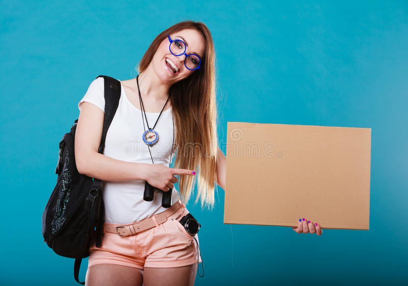 Woman hitchhiking with blank sign for your text. Travel and tourism active lifestyle concept. Woman tourist hitchhiking with blank sign for text on blue royalty free stock photo