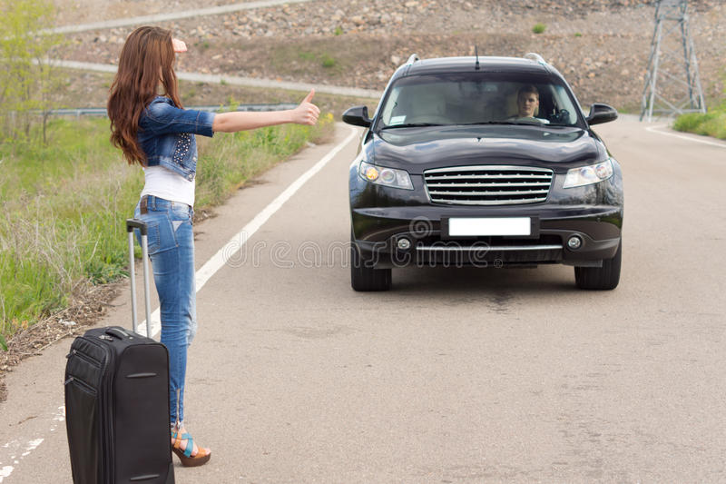 Woman hitchhiking after a breakdown with her car royalty free stock image