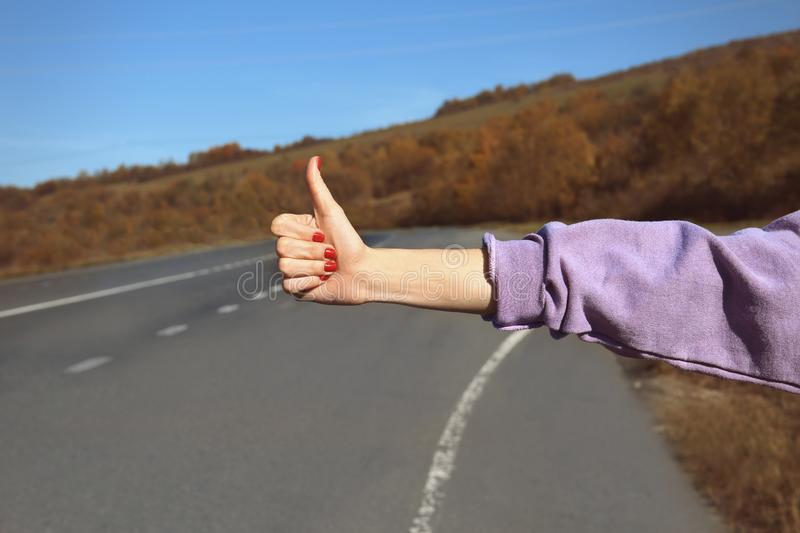 Woman hitchhiking on mountain road. Focus on hand royalty free stock images