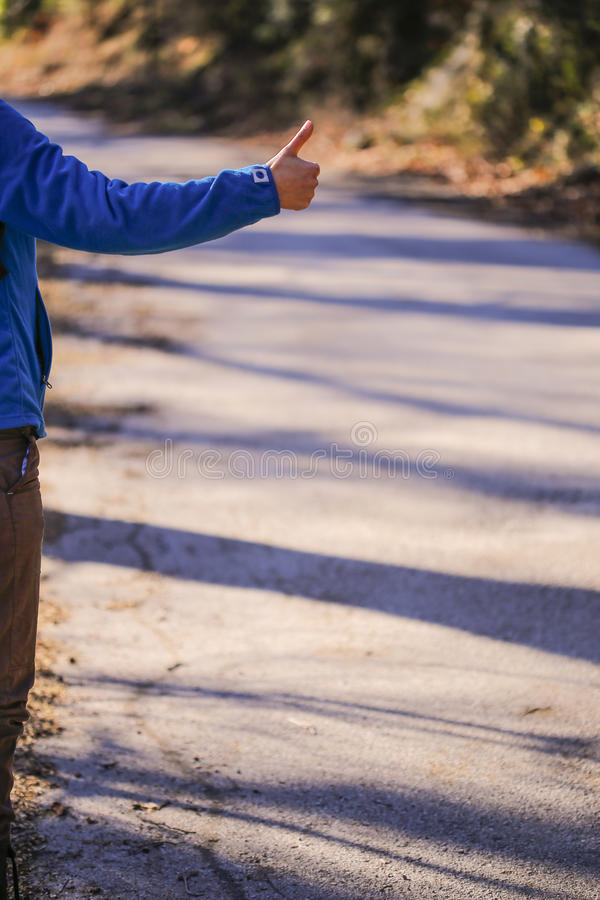 Woman hitchhiking on natural road. The Hitchhiking woman's hand on the beautiful road side royalty free stock image