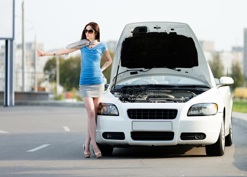Woman hitchhiking near the broken car. Woman hitchhiking near the opened hood of the broken car and waiting for assistance stock photos