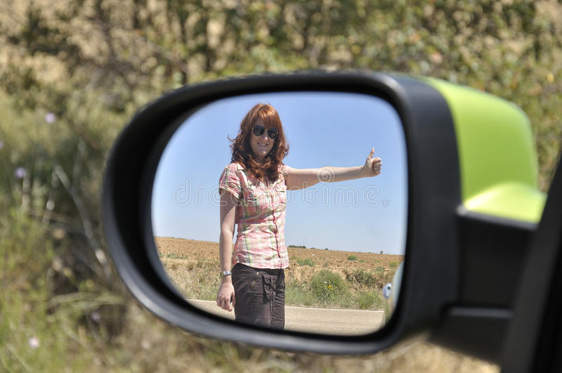Woman hitchhiking reflected in the rearview mirror. Red haired woman hitchhiking reflected in the rearview mirror of a green car stock images