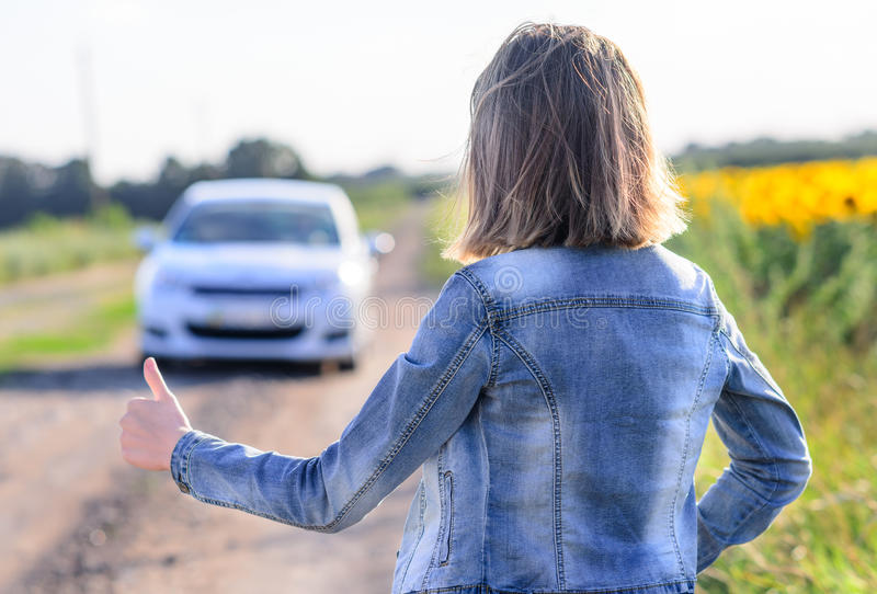 Woman hitchhiking on a rural road. Woman in denim jacket and jeans standing hitchhiking on a rural dirt road flagging down an approaching car, view from the rear stock photos