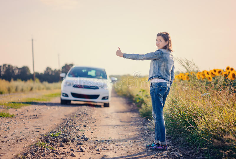Woman hitchhiking on a rural road. Woman in denim jacket and jeans standing hitchhiking on a rural dirt road flagging down an approaching car, view from the rear stock images