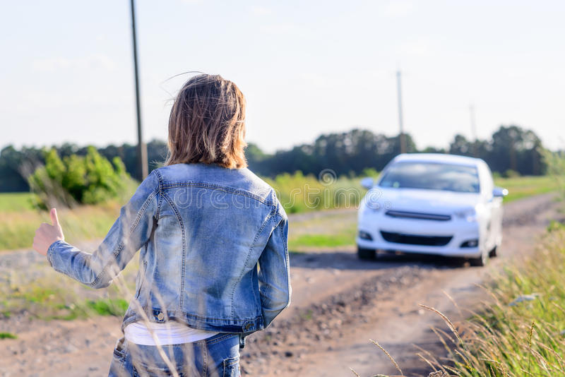 Woman hitchhiking on a rural road. Woman in denim jacket and jeans standing hitchhiking on a rural dirt road flagging down an approaching car, view from the rear royalty free stock photo