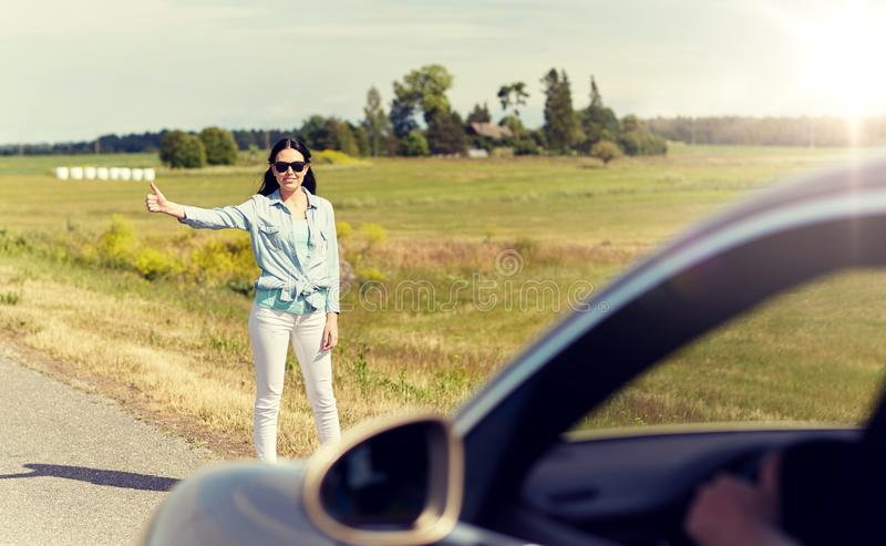 Woman hitchhiking and stopping car at countryside stock image