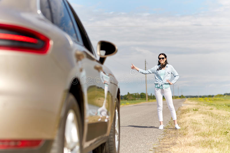 Woman hitchhiking and stopping car at countryside. Road trip, hitchhike, travel, gesture and people concept - woman hitchhiking and stopping car with thumbs up stock images